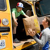 From the left: East Newton students Zach Greer and Ethan Brummett, both 14, help load donated school supplies onto a bus on Friday afternoon in Neosho during East Newton United's Stuff the Bus event. The supplies will be placed into backpacks for 150 children enrolled in the district's Food Pack program and also will be given to children with referrals from teachers.<br /> Globe | Laurie Sisk