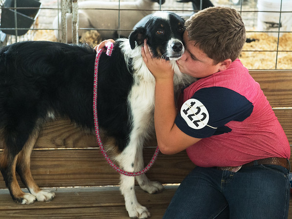 Charles Issac Sharp, 13, Columbus, hugs his dog Ace before judging at the Cherokee County Fair on Tuesday in Columbus.<br /> Globe | Roger Nomer