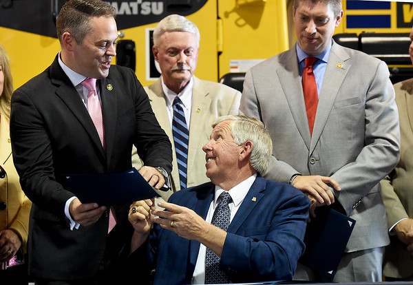 Missouri Gov. Mike Parson hands a signed copy of Missouri House Bill 2540 to Speaker Pro Tem Ejijah Haahr as Sen. Bill Eigel, right, looks on Thursday at Hartman & Co. in Springfield. Haahr and Eigel were both instrumental in shepherding the bill through the state legislature. The plan lowers Missouri's personal income tax rate from 5.9 percent to 5.5 percent effective Jan. 1. and allows personal income tax rates to to dip to 5.1 percent if the state hits revenue targets in the future.<br /> Globe | Laurie Sisk