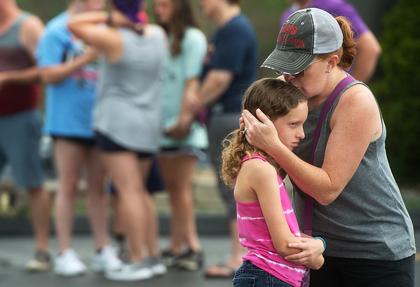 Sarah Irlmeier, Grimes, Iowa, kisses her daughter Paige, 10, after viewing a memorial to the victims of the duck boat accident in Branson on Friday.<br /> Globe | Roger Nomer