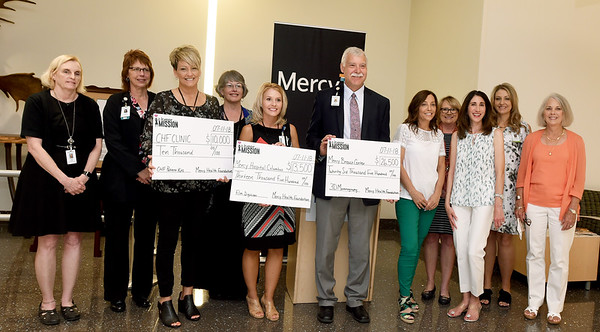 Recipients of three donations totaling $50,000 to Mercy departments pose with representatives of the Women on a Mission on Wednesday at Mercy Joplin. Women on a Mission is a Mercy Foundation collective that awards donations annually. This year's gifts will be used to help with an additional 3D mammography machine , cardiac discharge kits and a film digitizer for the Mercy Mobile Mammography van in Columbus.<br /> Globe | Laurie Sisk