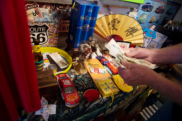 Supertam owner Larry Tamminen talks gifts he has received from Chinese visitors sign as they travel on Route 66 during an interview on June 21.<br /> Globe | Roger Nomer
