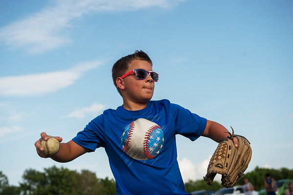 Isaac Wampler, 11, plays a game of catch before the fireworks at Missouri Southern on Thursday.<br /> Globe | Roger Nomer