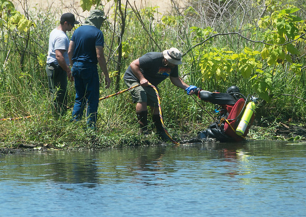 A dive crew searches a pond in Picher on Tuesday afternoon.<br /> Globe | Roger Nomer