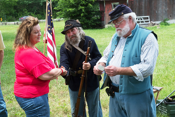 Linda Teeter presents a contribution to the Rader Farm Civil War Memorial Park from Urban Art Gallery to Paul Lewis and Steve Cottrell on Thursday during an open house at the park.<br /> Globe | Roger Nomer