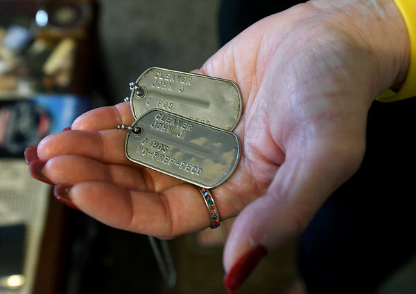 Gold Star mom Teresa Cleaver holds the dog tags her son, SSG John Cleaver wore when he was killed in Afghanistan in 2009. <br /> Globe | Laurie Sisk
