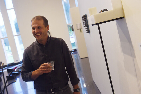 """Benjamin Cirgin, assistant professor of ceramics at Eastern Kentucky University, talks about his exhibit """"sample forms of compensation"""" at Missouri Southern's Spiva Gallery on Monday. The exhibit runs through Aug. 2.<br /> Globe 