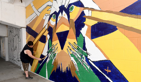 Burt Bucher works on a new mural on the walls of the 6th and Main Street underpass on Friday. Bucher, who designed the Lion-themed mural, is an associate professor of art at Missouri Southern. The project is made possible through the Downtown Joplin Alliance.<br /> Globe | Laurie Sisk