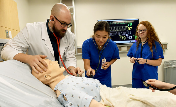 From the left: Sean Hickey, second year medical student at Kansas City University of Science and Biomedicine, assist sThomas Jefferson student Sonia Carlson and Joplin High School student Asia Huffman as they use stethoscopes on a patient simulator on Wednesday at KCU. The two were some of the 36 area high school students participating this summer in the Freeman Student Volunteer Futures Program, which exposes young people to the field of medicine. Upon completion of a variety of tasks, the student volunteers are then eligible for scholarships to colleges of their choice. The volunteers program is in its tenth year at Freeman.<br /> Globe | Laurie Sisk