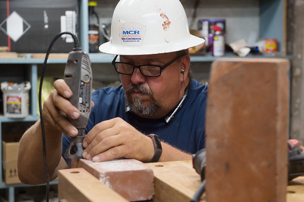 Mike Engstrom, with Mid-Continental Restoration, works on a brick at the Schifferdecker House on Wednesday.<br /> Globe | Roger Nomer