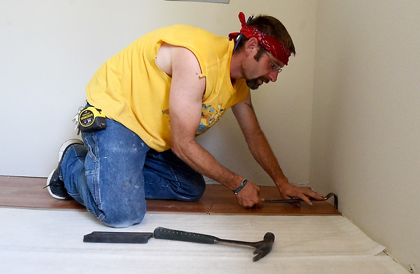 Carl Morgan, of K&M Construction, installs new laminate flooring in the upstairs portion of Forge on Thursday. Once remodeling is complete, the upstairs will feature 10 private rooms, a kitchen, common space, showers and more.<br /> Globe | Laurie Sisk