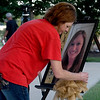 Longtime friend Shannon Phillips on Tuesday at Mercy Park places a portrait of Sarah Burton on an easel during a candleight vigil on the anniversary of Burton's disappearance. Burton was last seen on July 16, 2018, near 10th Street and Rex Avenue.<br /> Globe | Laurie Sisk