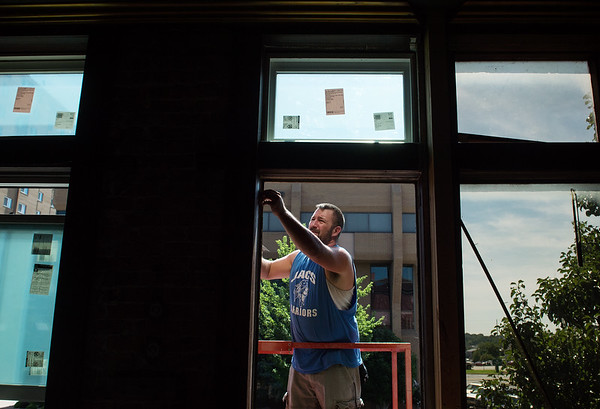 Jack Turner helps install new windows at Frosted Cakerie on Thursday morning.<br /> Globe | Roger Nomer
