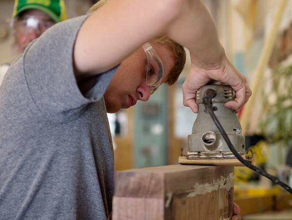 Kaden Padgett, 14, sands a cutting board during Camp AMPED on Wednesday at Crowder College in Neosho.<br /> Globe | Roger Nomer