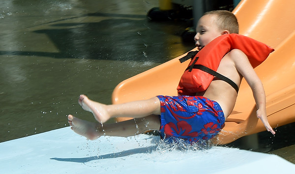 Five-year-old Alex Garber giggles as he takes a trip down the kiddie slide on Wednesday at Schifferdecker Pool.<br /> Globe | Laurie Sisk