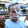 Brooklyn Keeling, of Goodman, spends some spare time at the fair blowing bubbles near the livestock pens on Thursday at the Newton County Fair in Neosho.<br /> Globe | Laurie Sisk
