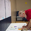 Howard Hogan writes down a comment on a facility improvement option on Tuesday during a community forum at West Central Elementary.<br /> Globe | Roger Nomer