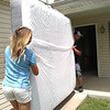 Della Croft (left), Director of Marketing for Joplimo Mattress, and Steve Guthrie (right), driver with Croft Bedding, help move the Jones' queen size mattress into their new duplex home on Tuesday in Carl Junction.   Kim Barker/JoplinGlobe