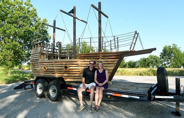 Dave and Sherri Johnson on Friday near Seneca, sit near the large cedar pirate ship playhouse that Dave constructed for their grandson, Julian Summerside, who turns two in September. The couple transported the ship Saturday to Little Rock, Ark., where Julian lives. The ship includes large sails (not pictured) and a treasure chest full of black pearls. <br /> Globe | Laurie Sisk