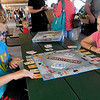 From the left, Siblings Ayden Truster, 11 and Ariel Truster, 9, both of Riverton, try out the new Webb City Opoly board game on Saturday at the Webb City Farmers Market. The game includes the classic features of the popular Monopoly game, but is customized to showcase local landmarks and businesses.<br /> Globe | Laurie Sisk