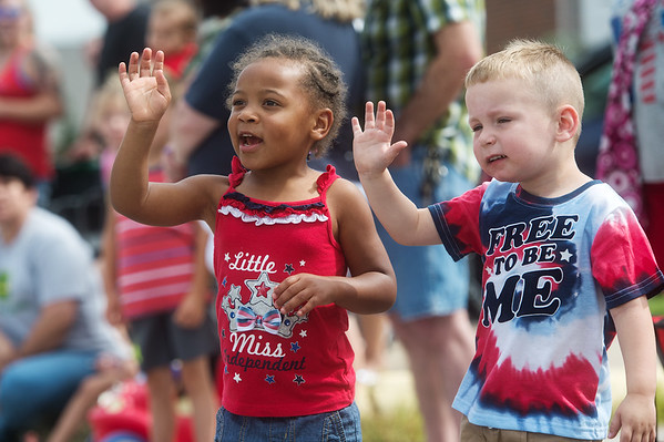 Friends Lillian Pittman and Joshua Breese, both 3, wave to fire engines during Thursday's Fourth of July parade in Carl Junction.<br /> Globe | Roger Nomer