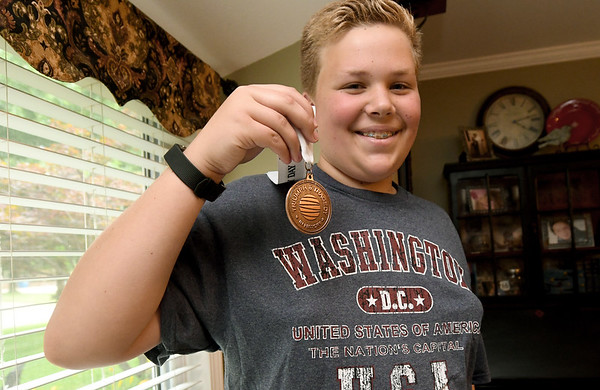 Thirteen-year-old documentary filmmaker Josef Schuller holds his National History Day medal he received after entering his documentary on the Korean War. The award winning documentary centers on action at Funchilin Pass.<br /> Globe | Laurie Sisk