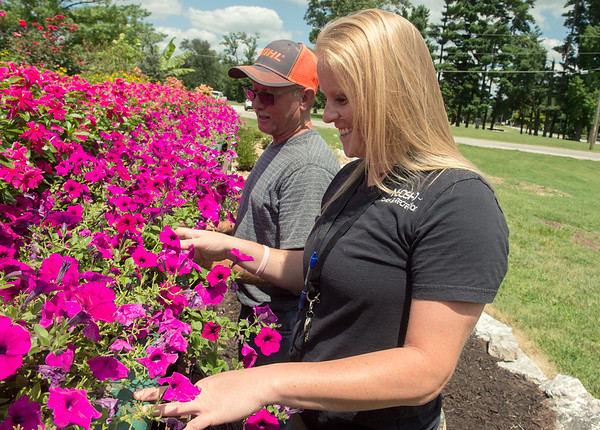 Kenny Balls, Neosho Parks and Rec supervisor, and Sally Pennington, Parks and Rec director, look at flowers in Neosho's flower box on Tuesday.<br /> Globe | Roger Nomer