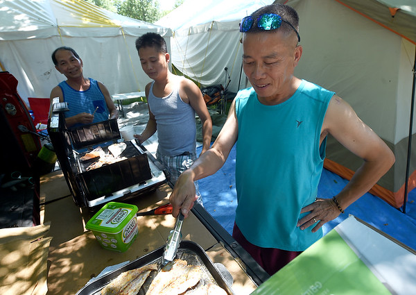 From the left: Toa Nguyen and his sons Kenny Nguyen and Michael Nguyen cook dried squid and fish at their campsite on Tuesday at Carthage's Congregation of the Mother of the Redeemer. The annual Marian Days begins Thursday at the church's campus.<br /> Globe | Laurie Sisk