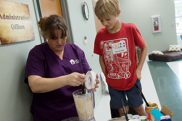 Leighton Oliver, 8, watches as Tianna Fisher, shelter services manager at the Joplin Humane Society, mixes a batch of pupsicles during Monday's Shelter Pals Pet Camp.<br /> Globe | Roger Nomer