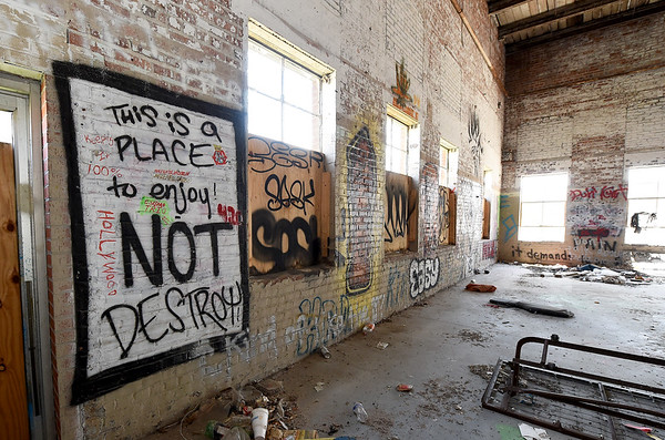 Pictured left, an ironic message is spray painted on the historic brick walls of the old Kansas Gas and Electric headquarters on North Locust Street in Pittsburg after taggers spray painted much of the historic brick inside the building.<br /> Globe | Laurie Sisk