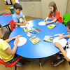 From the left: Bailee Muse, 7, Douglas Ball, 7 Cadence Hughes, 7 and Camden Ishimura, 6, create maracas using paper plates and uncooked popcorn during Art Feeds Paint Around the World on Saturday at St. Paul United Methodist Church.<br /> Globe | Laurie Sisk