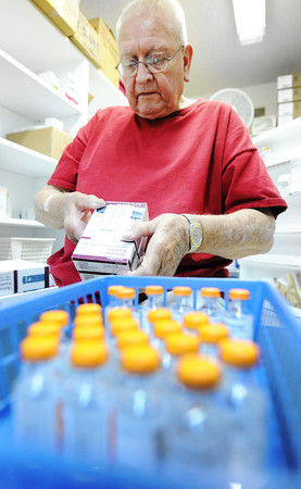 Globe/T. Rob Brown Chuck Elgin, of Joplin, a longtime volunteer, sorts prescription insulin by date at the Community Clinic Thursday afternoon, June 28, 2012.
