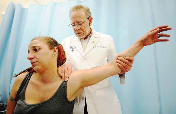 Globe/T. Rob Brown Patient Stormy Coonce, of Joplin, is examined by Dr. Roy Meek, chiropractic doctor, during a visit to the Community Clinic Thursday afternoon, June 28, 2012.