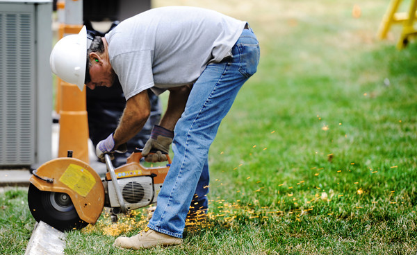 Globe/T. Rob Brown Andy Jones, job superintendent with MTS Contractors, of Springfield, cuts a piece of metal outside the Kelce School of Business recently at Pittsburg (Kan.) State University. Jones said his team was repairing or exposing lintels, the steel above the windows that supports bricks.