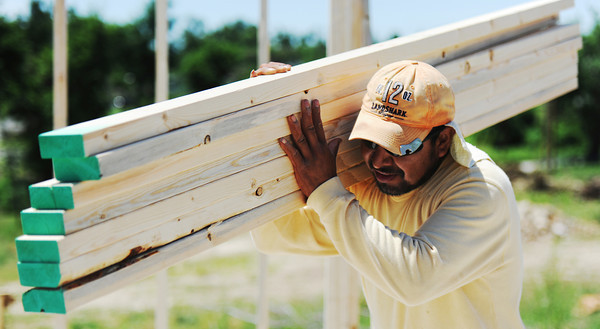 Globe/T. Rob Brown <br /> Oscar Ortiz, of Springdale, Ark., a framer with Regan Construction, carries a load of boards while framing a house in the 2700 block of South Moffet Avenue Tuesday morning, June 12, 2012.