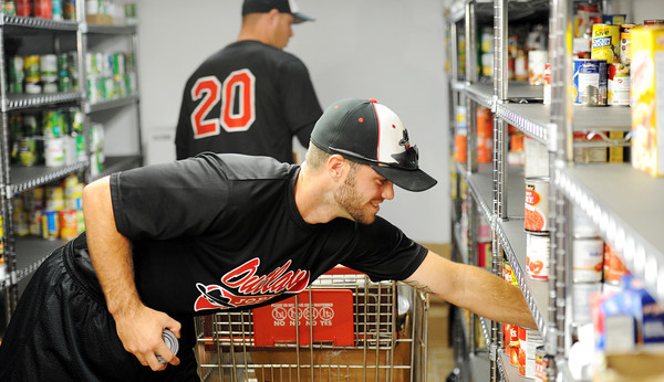 Globe/T. Rob Brown<br /> Joplin Outlaws baseball players second baseman Taylor Eaves, foreground, of Beaumont, Texas, and pitcher Eddie Smith, of Tuscaloosa, Ala., sort canned goods Monday afternoon, June 11, 2012, at Soul's Harbor's pantry in Joplin.