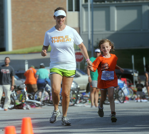 Globe/Roger Nomer<br /> Rachelle Smith guides her daughter Taegan, 7, to the finish line at the Big Time Youth Triathlon on Saturday.