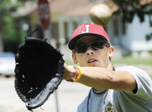 Globe/T. Rob Brown Gavin Williamson, 16, plays catch with a friend in front of his Joplin home to enjoy the weather and practice Thursday afternoon June 14, 2012. Their previous family home was picked up at the foundation, with them inside, and dropped during the May 22, 2011, tornado. Williamson is also a member of the Joplin Miners and Joplin High School baseball teams.