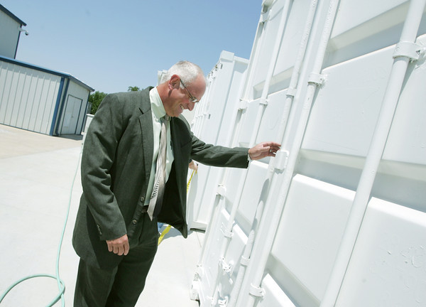 Globe/Roger Nomer<br /> Randy Moore, president of EaglePicher Technologies, opens the door to a trailer of batteries storing energy from a wind turbine during a tour of the company's facility on Thursday.