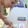 Globe/Roger Nomer<br /> Ashley Cron, Joplin, creates a luminaria in honor of her husband's grandmother at the Joplin Relay for Life in Cunningham Park on Saturday.