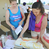 Globe/Roger Nomer<br /> Jolena Nussel, Webb City, right, and Kirstie Kelly, Carthage, set up the silent auction at the Joplin Relay for Life in Cunningham Park on Saturday.