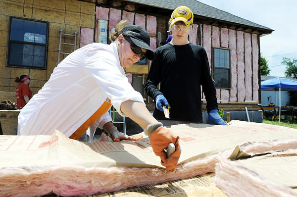 Globe/T. Rob Brown<br /> Pam Miller, left, and Scotty Griswold, 14, both of Baton Rouge, La., and volunteers with the Christian Church Disciples of Christ group from Baton Rouge, cut insulation for a Rebuild Joplin project in the 2000 block of Pennsylvania Avenue Wednesday afternoon, June 6, 2012.