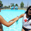Globe/T. Rob Brown Ewert Family Aquatic Center lifeguards Lauren Dobrauc, left, 18, of Carthage, sprays as Katie Rickey, 17, of Carl Junction, reacts to the cold application of spray-on 50 SPF sunscreen at the start of their shift Monday afternoon, at the Joplin aquatic center.