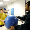 "Globe/T. Rob Brown<br /> Samantha ""Sam"" Evans, left, of Joplin, senior criminal justice major, loans out an exercise ball to gymgoer Traé Henderson, of Joplin, senior health promotion major, Thursday afternoon, June 7, 2012, at Missouri Southern State University. Evans works at the on-campus job to help defer some of her education costs."