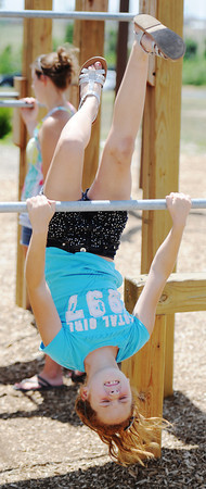 Globe/T. Rob Brown Asia Huffman, 10, of Joplin, performs a flip on a metal bar Wednesday afternoon, June 20, 2012, at Cunningham Park in Joplin.