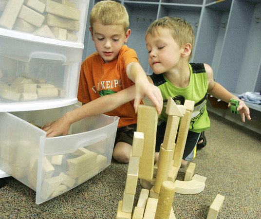 Globe/Roger Nomer<br /> Landon Stribling, left, and Caden Thompson, both entering kindergarten this year, get crossed up while building a block chocolate chip factory at Cecil Floyd summer school on Friday.