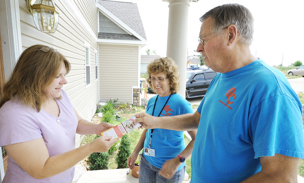 Globe/T. Rob Brown Diane Huddleston, left, of Joplin, gets a services brochure from community crisis workers Teri Nunnally and Tom Tiegreen, right, Wednesday afternoon, June 13, 2012, at her front door.