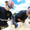 Globe/T. Rob Brown Clay Arft, left, hammers in a nail as John McDaniel, both driver/engineers with the Joplin Fire Department, holds the board steady as they create a strut system Tuesday afternoon, June 19, 2012, during a structural collapse class for the Joplin Fire Department's Special Operations Team outside an abandoned business on Main Street, near 34th Street.