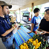 Globe/T. Rob Brown<br /> Shon Bishop, left, a 2501 Program assistant from Mt. Vernon and with the Lincoln University Extension, speaks with food growers Nhia Xiong, right, and his son Kong Xiong, both of Anderson, Friday, June 1, 2012, at the Webb City Farmer's Market. Bishop helps people identify issues with their trees and plants as well as offer advice on how to treat for insects, infections or other harmful plantlife issues.