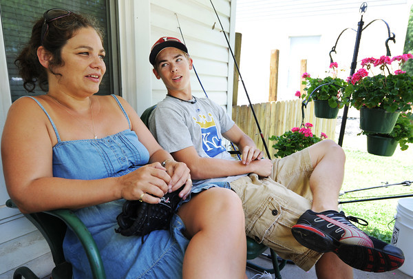 Globe/T. Rob Brown Andrea Holseth and her 16-year-old son Gavin Williamson sit on the front porch of their Joplin home to enjoy the weather, in the shade, and talk Thursday afternoon June 14, 2012. Their previous family home was picked up at the foundation, with them inside, and dropped during the May 22, 2011, tornado.